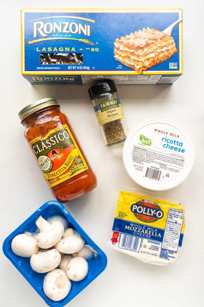 Ingredients on table, lasagna, tomato sauce, oregano, cheeses, and mushrooms.