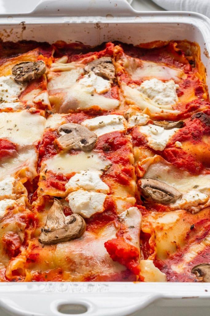 cheesy lasagna with mushrooms in baking dish.